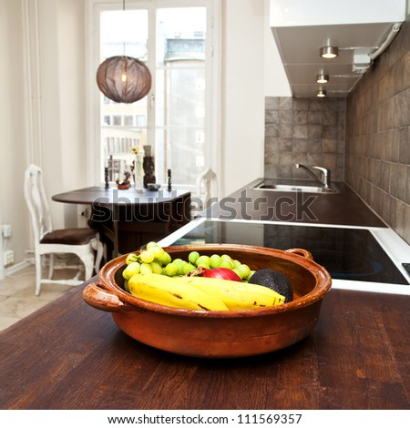 interior of a kitchen with a bowl of fruit in the foreground - stock photo