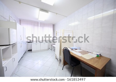Interior of a light doctors consulting room with table, cabinet and folding screen - stock photo