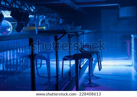 Interior of a modern bar with moody blue lighting and a row of contemporary bar stools in front of a reflective counter in a nightclub - stock photo
