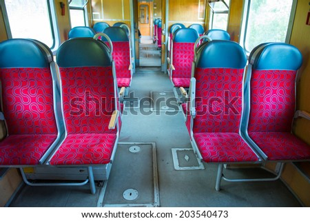 Interior of a modern train with windows and empty red seats - stock photo
