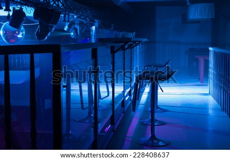 Interior of a pub or nightclub with moody blue lighting and stylish bar stools reflected in the counter, architectural background with nobody in frame - stock photo