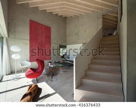 Interior of a villa, modern living room with red armchair, concrete walls - stock photo