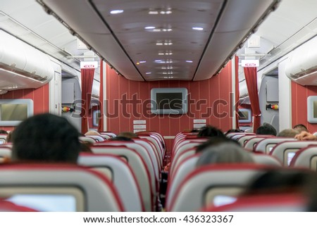 Interior of aircraft with sittings passengers. Inside flying air plane with traveling people. - stock photo