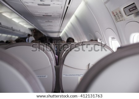 Interior of airplane with passengers on seats - stock photo