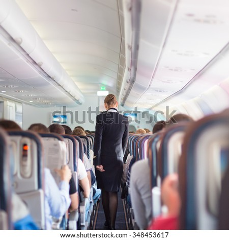 Interior of airplane with passengers on seats during flight. Stewardess in dark blue uniform walking the aisle. Square composition. - stock photo