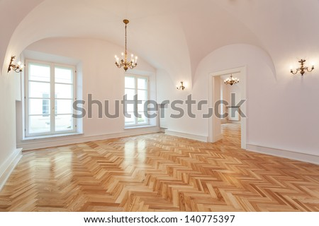 Interior of an empty palace with a wooden floor and chandelier. - stock photo