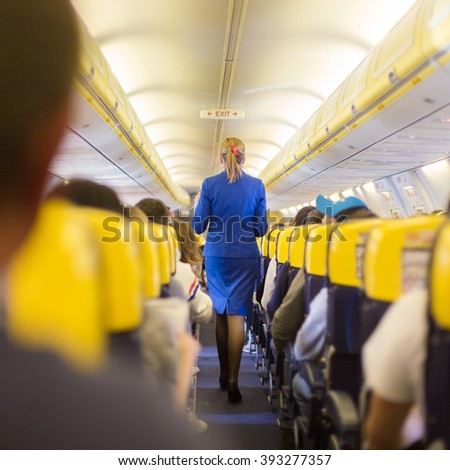 Interior of commercial airplane with passengers on seats during flight. Stewardess in blue uniform walking the aisle. Square composition. - stock photo