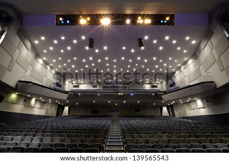 Interior of empty cinema auditorium with lines of chairs. - stock photo