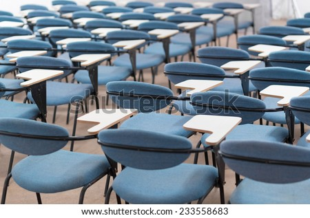 Interior of empty conference hall with blue velvet chairs with small desks for writing notes. - stock photo