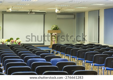 Interior of Empty Conference Hall With Lines of Blue Chairs in Front of Stage with Screen.Horizontal Image Composition - stock photo