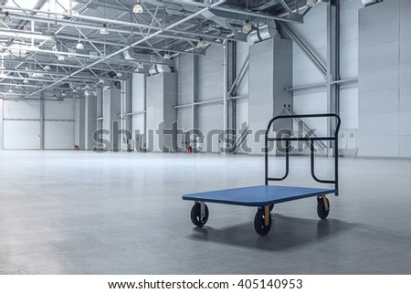 Interior of empty warehouse with a cart - stock photo