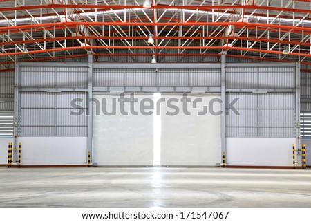 interior of factory with shutter door, day  scene.  - stock photo