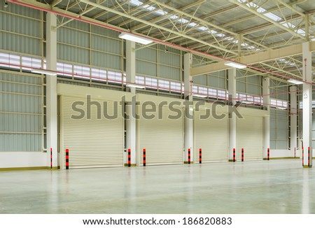 Interior of factory with shutter door, night time. - stock photo