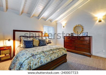 Interior of home. Beautiful classic master bedroom with vaulted white wood ceiling and wood dresser. - stock photo