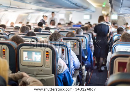 Interior of large passengers airplane with people on seats and stewardess in uniform walking the aisle.  - stock photo