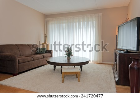 Interior of living room in private residence furnished with table sofa television and decor - stock photo