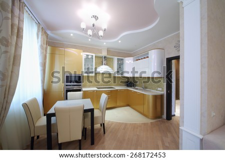 Interior of luxurious kitchen with golden cabinets in the apartment - stock photo