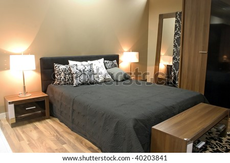 Interior of modern bedroom with furniture and mirrors in warm orange colors. - stock photo