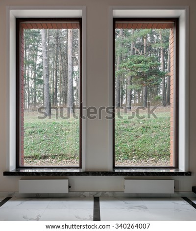 Interior of modern empty space with big windows and forest on the background  - stock photo