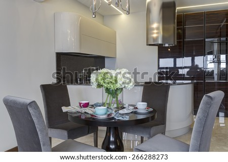Interior of modern kitchen with round table and four chairs - stock photo