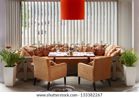 Interior of modern restaurant with a big orange sofa two orange chairs, an orange lamp and the laid table - stock photo