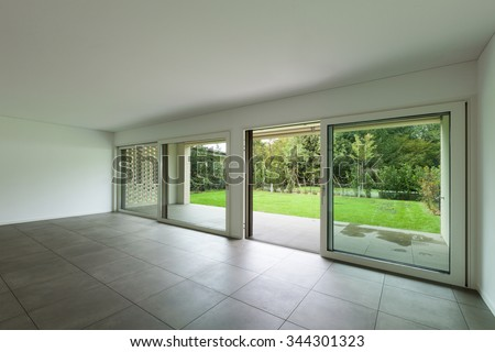 interior of new apartment, empty hall with window, tiled floor - stock photo