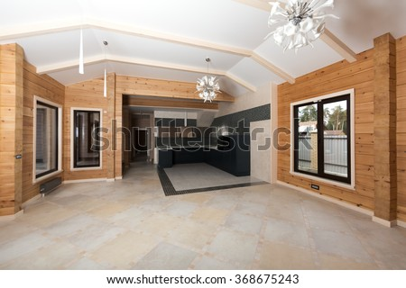 Interior of new wooden eco house built from cedar. Spacious studio. Fashionable modern black kitchen. Italian design white chandeliers. - stock photo