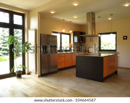 Interior of spacious modern house: well-lit kitchen - stock photo