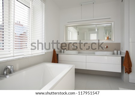 Interior of spacious, plain and white bathroom - stock photo