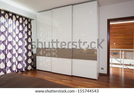 Interior of stylish bright bedroom with wardrobe - stock photo