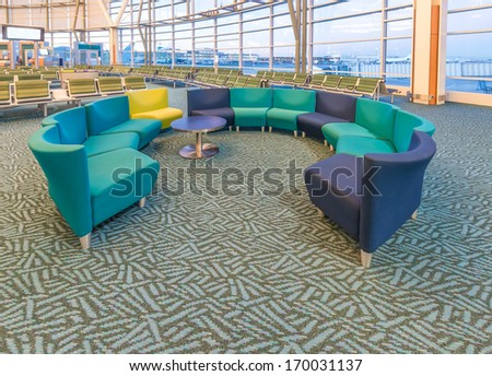 Interior of the airport terminal with some benches. - stock photo
