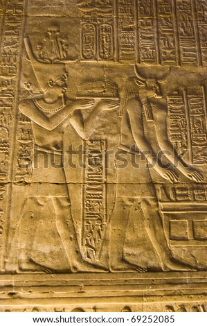 Interior of the ancient egyptian Temple of Horus at Edfu, Egypt.  Hieroglyphic carving showing the Pharaoh with the bull headed god Apis. - stock photo
