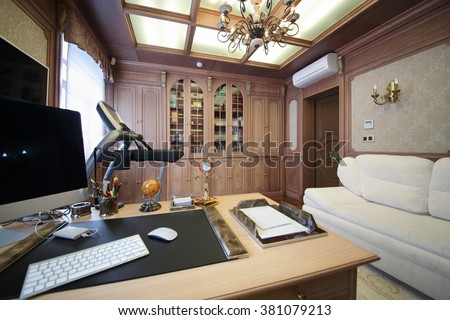 Interior of the modern cabinet in the English style with desktop, wooden bookcase and white sofa  - stock photo