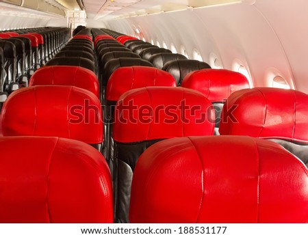 interior of the passenger airplane with red and black leather seat  - stock photo