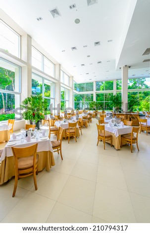 Interior of the tropical, caribbean restaurant with nicely served and decorated tables at the luxury resort. Vertical. - stock photo