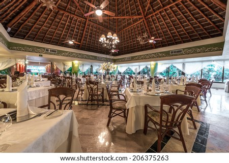 Interior of the tropical, caribbean restaurant with nicely served and decorated tables of the luxury resort. - stock photo