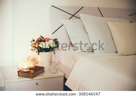 Interior of white bedroom, new linens on the bed, the room at the hotel. Bedside table decor with candles and pillows closeup. - stock photo
