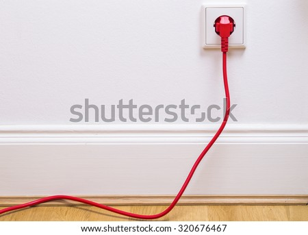 Interior outlet with a red plugged in cable  - stock photo