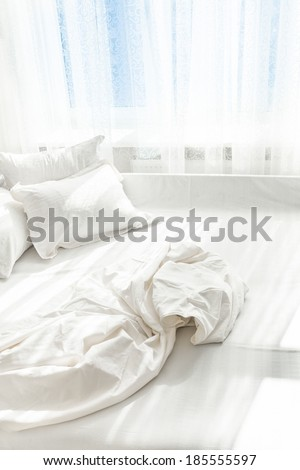 Interior photo of unmade bed against window - stock photo