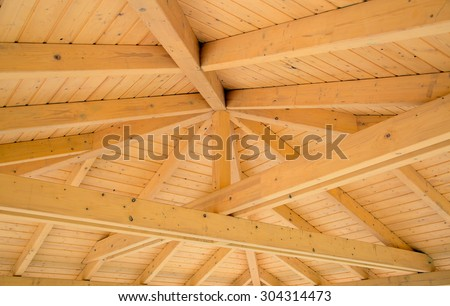 Interior roof beams on a wooden structure - stock photo