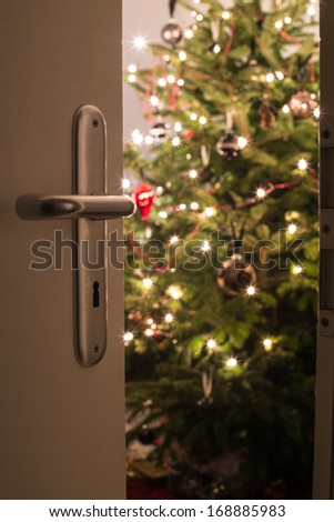 Interior shot of a modern living room with a Christmas tree as seen through the living room door - stock photo