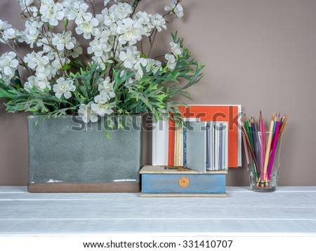 Interior still-life, artificial flower vase, books on wooden table top/ home improvement concept - stock photo