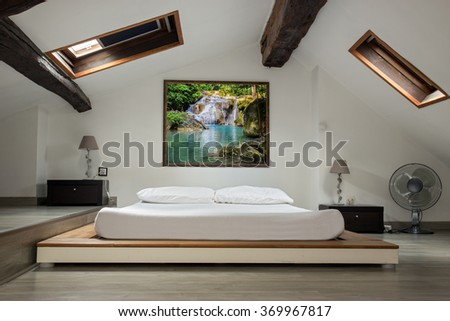 interior view of a bedroom in the attic room. Bedroom in the attic with a picture of nature with a waterfall over the bed. Romantic bedroom with a romantic painting on the wall. Empty roof bedroom. - stock photo
