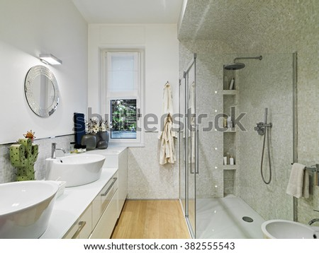 interior view of a modern bathroom with glass shower cubicle and wood floor - stock photo