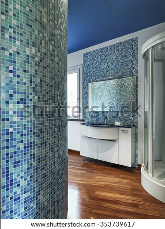 interior view of a modern bathroom with mosaic tile, wood floor and ceiling painted of blue - stock photo