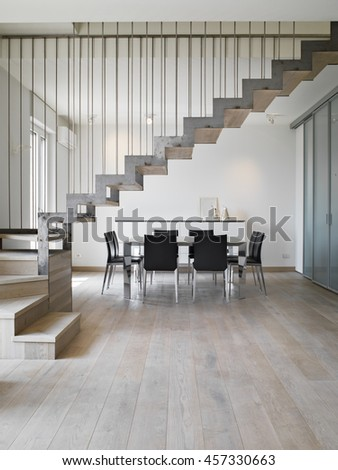 interior view of a modern dining room with dining table and iron staircase the floor isa made of wood - stock photo