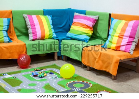 Interior with colorful wooden sofa covered by color blankets, nursery room - stock photo