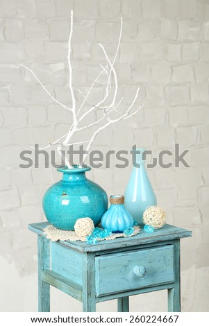 Interior with decorative vases and branch twig on nightstand and white brick wall background - stock photo