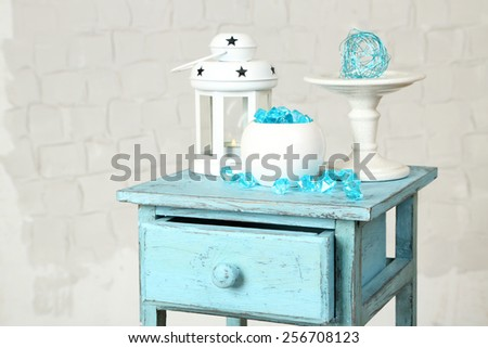 Interior with decorative vases and lantern on nightstand and white brick wall background - stock photo