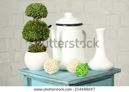 Interior with decorative vases plant on nightstand and white brick wall background - stock photo